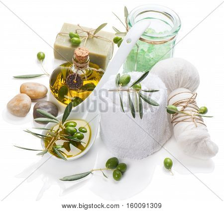 Natural spa setting and treatment with olive oil green olives essential salt herbal ball zen stones and cotton towel isolated on white background.