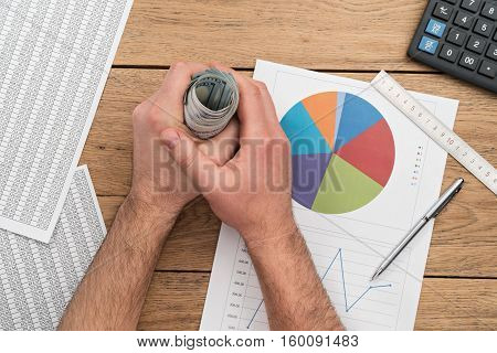 Business still-life. Male arms carry the roll of dollars putting his hands on the table which is a calculator ruler pen and various graphs and charts