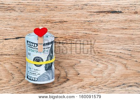Gift roll of dollars tied with yellow rubber band with clothespin in the shape of a heart on a wooden table