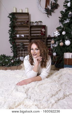 Woman lying on the floor near a Christmas tree dressed up