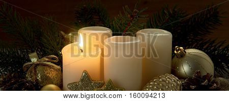 Christmas background with four white advent candles and golden decoration. Four advent candles with first candle lit.