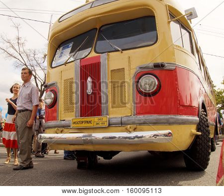 MOSCOW, RUSSIA - August 13, 2016: Guy and girl in clothes of the 1950's next to the retro city bus ZIS 155. Festive occasion of the Moscow bus on the Frunze Embankment. August 13, 2016 in Moscow, Russia