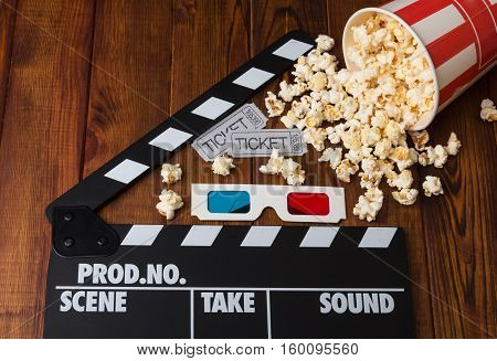 Movie tickets, 3D glasses, paper box spilled popcorn and movie clapper on a wooden background