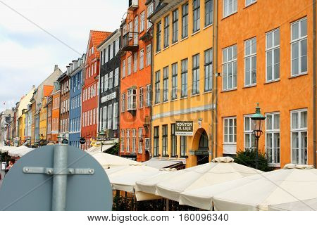 Copenhagen, aug 21. 2016 - Nyhavn street sign with bars and sun umbrellas at Nyhavn place Copenhagen Denmark.