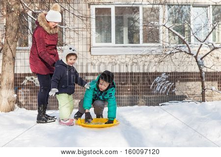 Family resting outdoors in winter grandmother with grandchildren ride down the hills on saucer sled in winter time