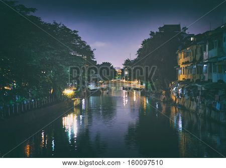 Night landscape of Klong Ong Ang canal in touristic center of Bangkok, Thailand. Night illumination of buildings and bridges.