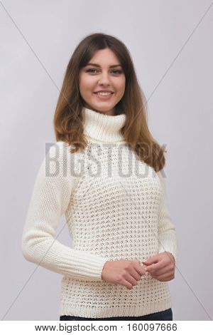 Gorgeous young brunette woman in warm knitted sweater on light grey background