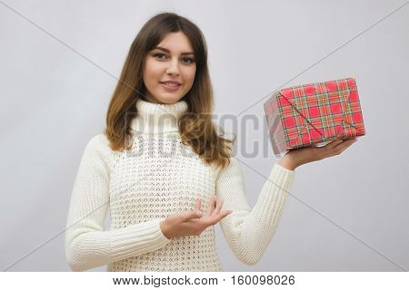 Woman in white sweater holding gift box over gray background