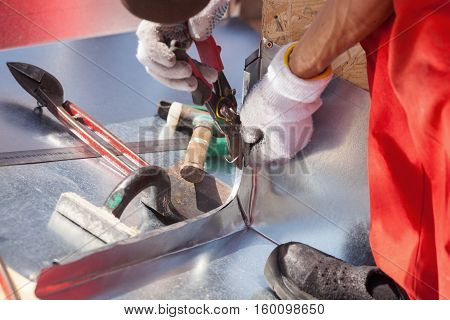 Roofer builder worker finishing folding a metal sheet using metal shears