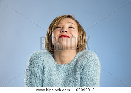 candid portrait of young beautiful and sweet woman in blue pullover smiling happy and cheerful in friendly face expression isolated on blue background in happiness concept