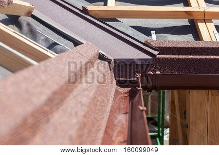 New asphalt shingle roof with brown rain gutter wooden beams and vapour control layer