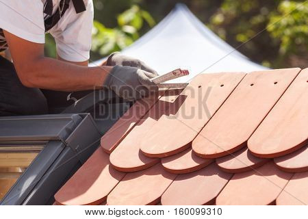 Natural roof tile instaalation. Roofer builder worker use ruller to measure the distance between the tiles