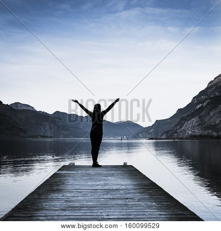 Background as epic mountain landscape. Female figure on a wooden pier. Book cover. Bleach bypass effekt.