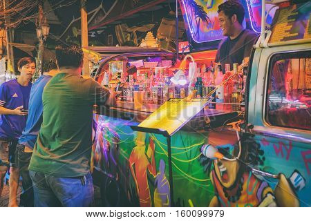 Bangkok, Thailand - January 11, 2016: Rambuttri Alley at night popular food street close to Khaosan road and district for back packer and budget tourist. Mobile bar with alcohol and smiling barman