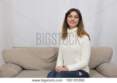 Portrait of young woman sitting on couch in her living room