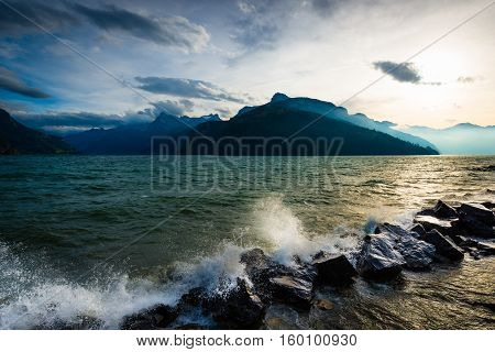 Storm and wind on the lake of Swiss Alps. Splash of waves in the setting sun.