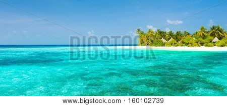 Maldives. Island in the ocean. Palm trees on the white sand beach. Turquoise water of the lagoon. Roof bungalow suite. Bleach Bypass effect.
