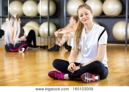 Full length portrait of confident young woman sitting cross legged in fitness center