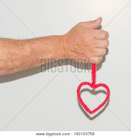Man's hand holding in a fist symbol of the heart woven from threads of red color.