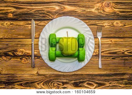 Dumbbells, ball and expander on a plate as a breakfast, concept of healthy lifestyle, on a wooden table