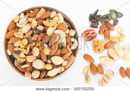 Mixed nuts top view: Pistachios, peanuts, walnuts, almonds, hazelnuts, Brazil nuts, pumpkin seed and cashews in wooden bowl