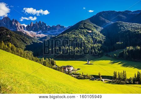 The symbol of the valley Val di Funes - church of Santa Maddalena. Forested mountains surrounded by green Alpine meadows.  Sunny day in Dolomites, Tirol