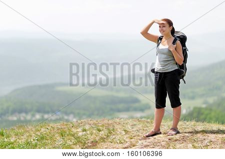 Young Female Hiker With Backpack On Hilltop