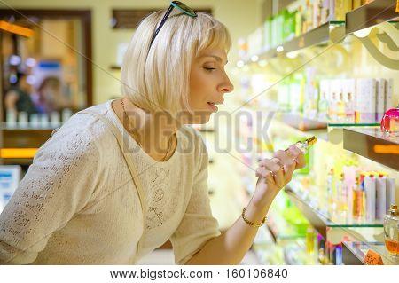 Beautiful caucasian woman selecting perfume in the store