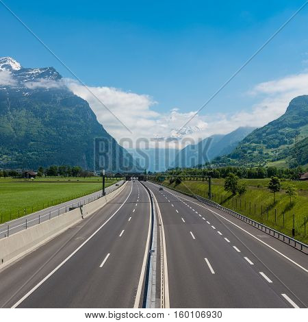 Empty highway is among the alpine mountains and fields. Path of Switzerland towards Italy St. Gotthard tunnel