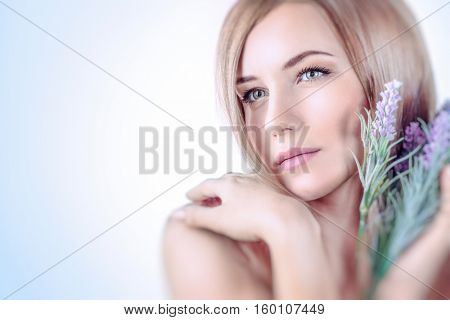 Closeup portrait of a beautiful gentle woman with lavender flower bouquet over white and blue background, aroma therapy, enjoying dayspa