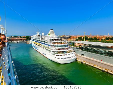 Venice, Italy - June 06, 2015: Cruise liner AIDA Vita docked at the port of Venice, Italy on a background of the roofs and another cruise ship on June 06, 2015