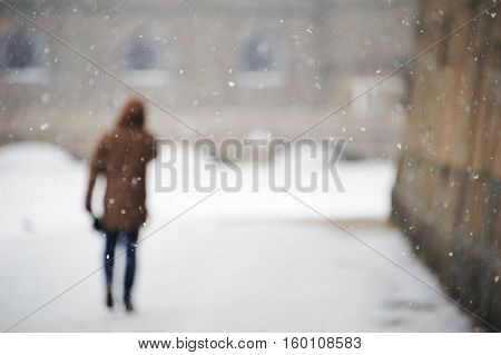 Blurred abstract background - the town buildings people walking on the street falling snowflakes