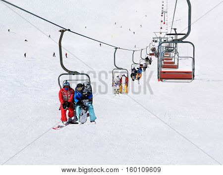 Chairlift (ski lift) transport skiers and snowboarders up a snowy downhill at winter ski snow Alpine resort active seasonal outside sports background