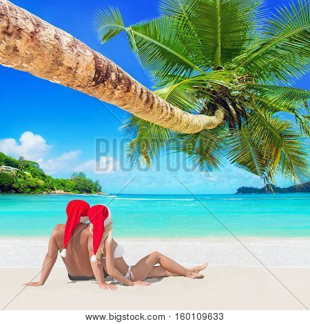 Romantic couple in red Christmas Santa hats sunbathe at tropical palm sandy island beach Seychelles Indian Ocean. New Year ans Xmas holiday travel destinations concept