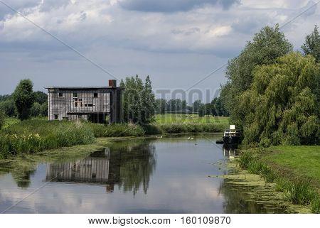 Run-down shed on the bank of the river Giessen near Hoornaar in the Dutch region Alblasserwaard poster