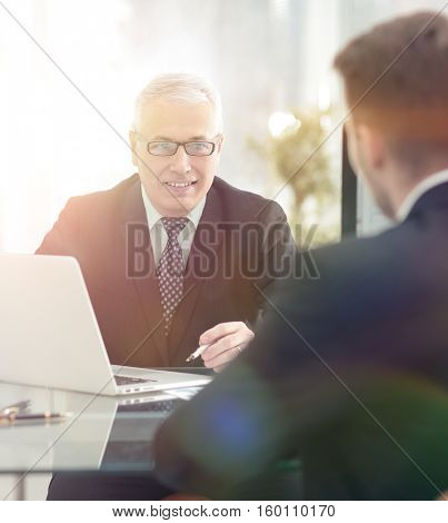 Business partners discussing in meeting hall with their collegue
