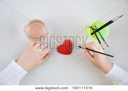 hands of a young girl painted handmade gift in the form of Heart