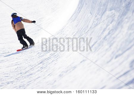 Snowboarder in halfpipe, focus on snow