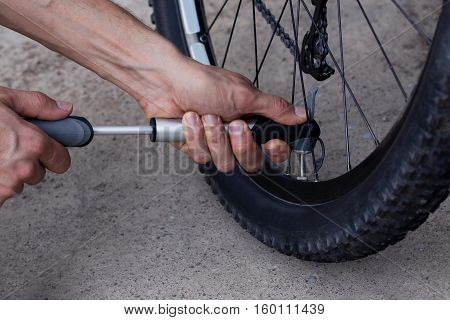 The young man inflates bicycle wheel using a pump