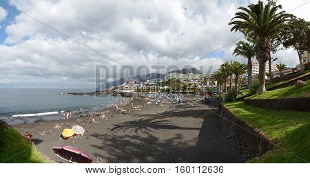 PUERTO DE SANTIAGO, SPAIN - OCTOBER 06: Tourists are resting on the Arena beach in cloudy day on October 06, 2014 in Puerto de Santiago, Tenerife Island, Canary Islands, Spain.