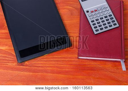 Black tablet calculator and notebook on the table