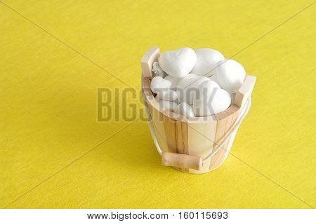 Valentines day. A wooden bucket filled with polystyrene hearts isolated against a yellow background