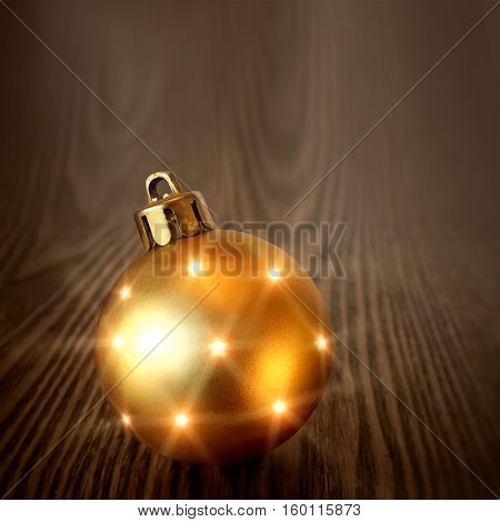 Christmas golden ball on a wooden background