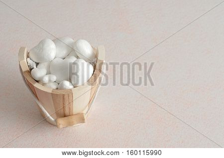 Valentines day. A wooden bucket filled with polystyrene hearts isolated against a white background