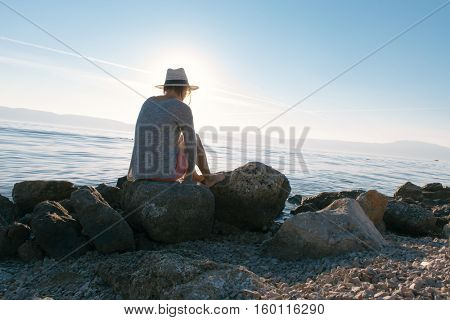 Young woman wearing hat, looking at beautiful view of sea