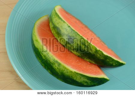 Close up of two slices of seedless watermelon on blue plate