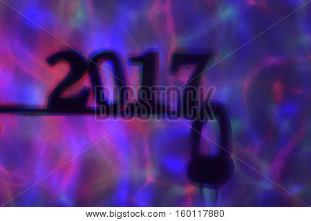 colorful lights projected on a wall and the shadow of the number 2017, as the new year, and a pair of headphones in a dance club