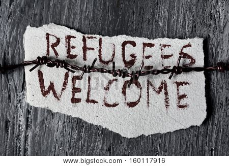closeup of a barbed wire and a piece of paper with the text refugees welcome handwritten in it on a rustic wooden surface