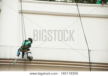 BANGKOK, THAILAND-NOVEMBER 18,2016 : Unidentified Glass cleaner abseiling from a tall building. Window cleaners at work on skyscraper, Bangkok , Middle of Thailand.