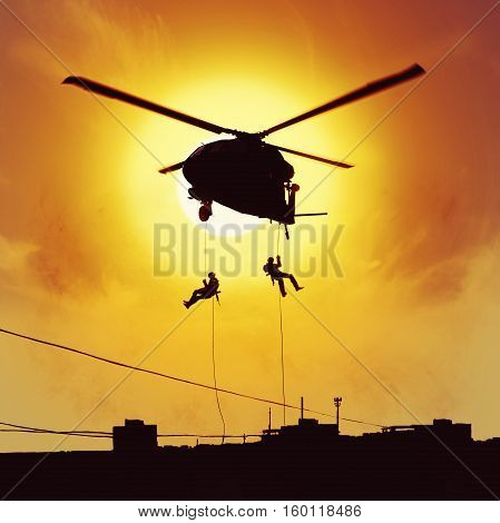 Special forces operators are fastroping from helicopter
